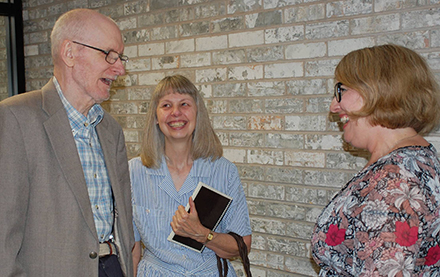 Dr. Doug Baker and his wife, Linda, laugh with English Associate Professor Jennifer Poynter-Thompson.