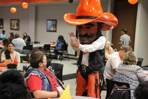Pistol Pete visits with a student at Orange Crush